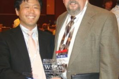 K. Adachi of Tohoku University accepts the Best Poster Award from Peter Blau, Oak Ridge National Laboratory