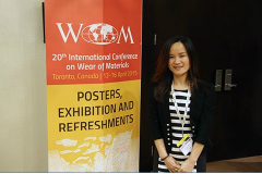 Laney Zhou poses with WOM banner